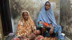 Mohammed Umar's first wife, Mainuna Shuaibu, left, who married the impoverished bricklayer when she was 14, and Maryam Adam, who became his second wife when she was 15, and two of their children at their home in Kano, Nigeria. (Robyn Dixon / Los Angeles Times)